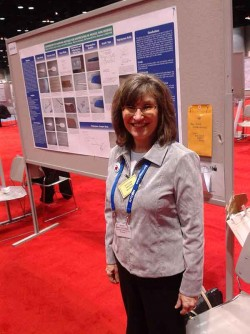 photo of Mary Stellmack, Senior Research Chemist with McCrone Associates, standing in front of her party-knife poster at Pittcon
