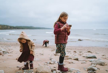 girls collecting shells and sand