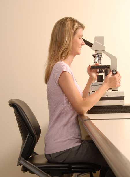 Correcting her posture at the microscope